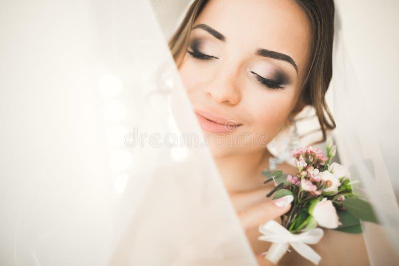 Ursnygg brud i ämbetsdräkten som poserar och förbereder sig för framsidan för bröllopceremoni i ett rum royaltyfria bilder