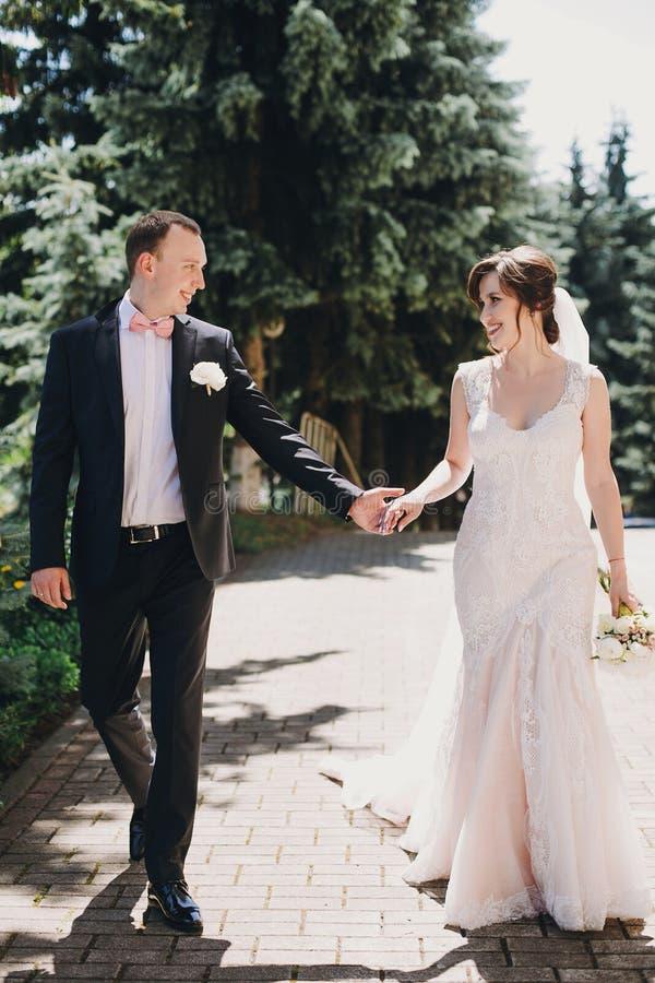 Ursnygg brud, i att förbluffa kappan och den stilfulla brudgummen som går och ler i solig stadsgata Härliga lyckliga brölloppar s arkivfoto