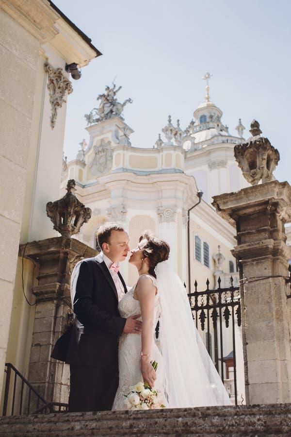 Ursnygg brud, i att förbluffa kappan och den stilfulla brudgummen som kysser och omfamnar i solig gata på gammal byggnad Härligt  arkivfoton