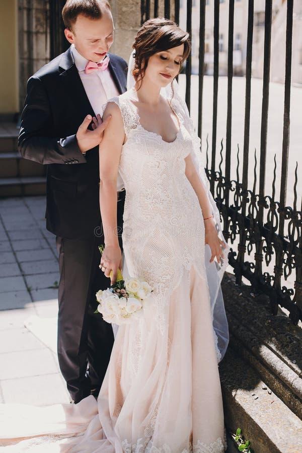 Ursnygg brud, i att förbluffa kappan och den stilfulla brudgummen som omfamnar i solig gata på gammal byggnad Härliga lyckliga br arkivfoto