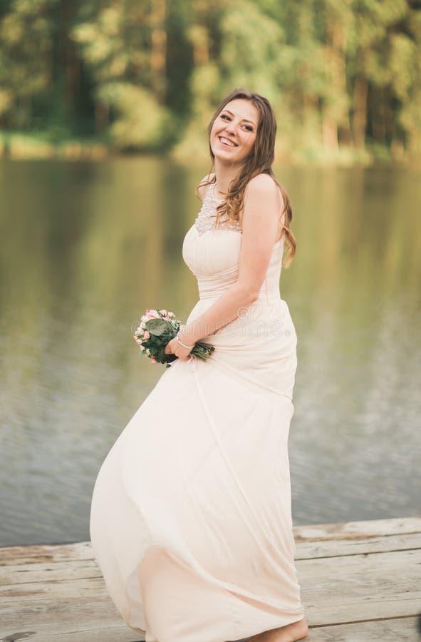 Download Ursnygg Brud I Den Hållande Buketten För Elegant Klänning Som Poserar Nära Skog Och Sjön Arkivfoto - Bild av caucasian, förälskelse: 78726602