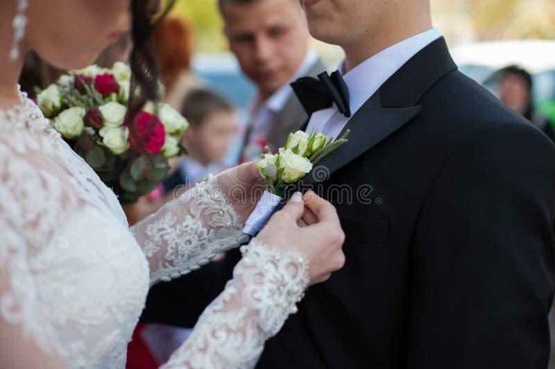 Ursnygg brud i den vita klänningen för tappning som sätter på boutonniere på arkivfoton
