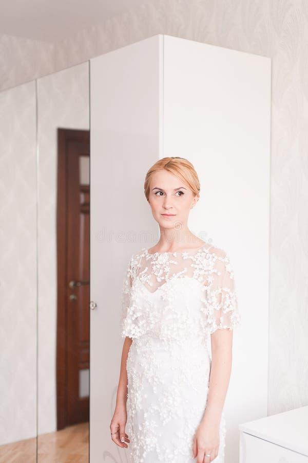 Ursnygg brud med bröllopbukettmakeup och frisyr i hemmastadd väntande på brudgum för brud- klänning royaltyfri fotografi