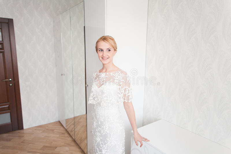 Ursnygg brud med bröllopbukettmakeup och frisyr i hemmastadd väntande på brudgum för brud- klänning arkivbilder