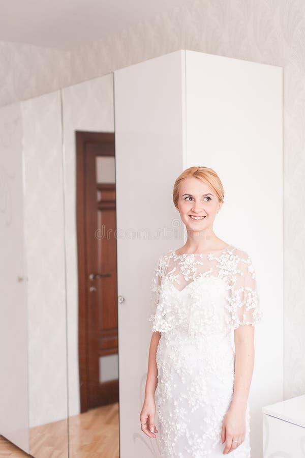 Ursnygg brud med bröllopbukettmakeup och frisyr i hemmastadd väntande på brudgum för brud- klänning royaltyfria foton