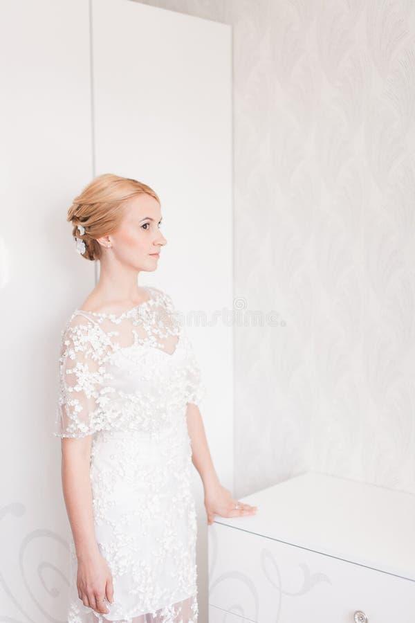 Ursnygg brud med bröllopbukettmakeup och frisyr i hemmastadd väntande på brudgum för brud- klänning royaltyfri foto