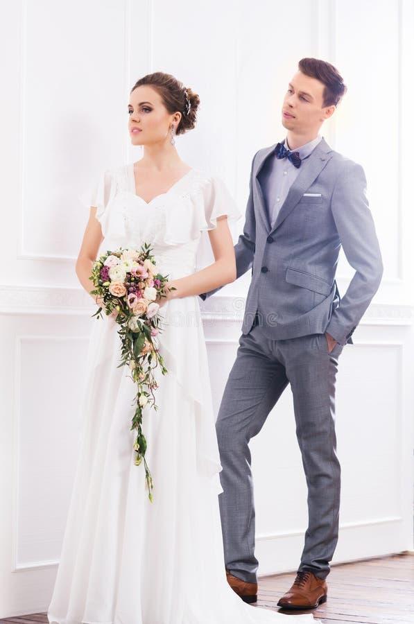 Ursnygg brud med en liten bukett och en stilig brudgum i retro inre royaltyfri foto