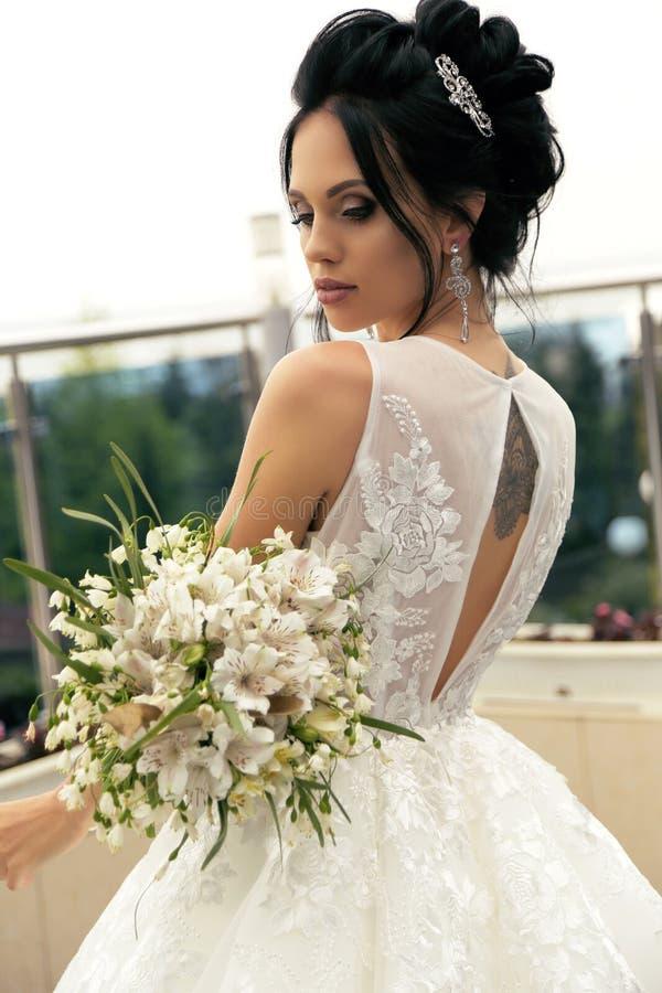 Ursnygg brud med mörkt hår i lyxig bröllopsklänning och acc arkivfoto