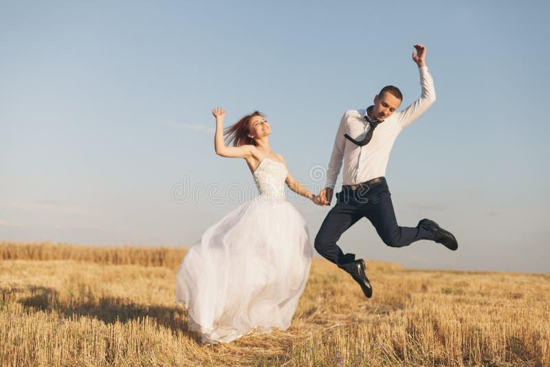 Ursnygg brud och brudgum i vetefält Lycka och förbindelse Kvinna i den vita klänningmannen i den vita skjortan och bandet fotografering för bildbyråer