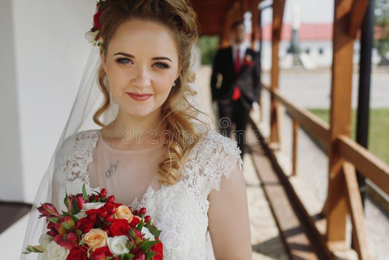 Ursnygg brud och brudgum som utomhus ler och poserar lyx gifta sig royaltyfri fotografi