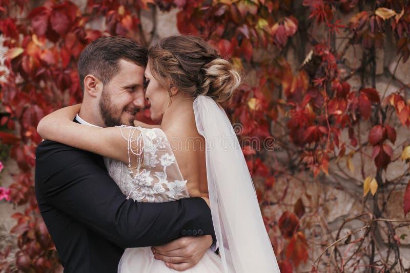 Ursnygg brud och stilfull brudgum som kramar och ler försiktigt på royaltyfri bild