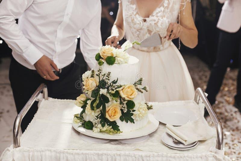 Ursnygg brud och stilfull brudgum som tillsammans klipper vitt bröllop royaltyfria bilder