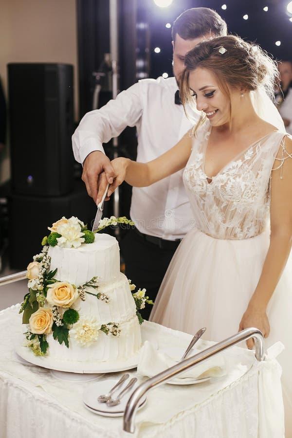 Ursnygg brud och stilfull brudgum som tillsammans klipper vitt bröllop royaltyfri bild