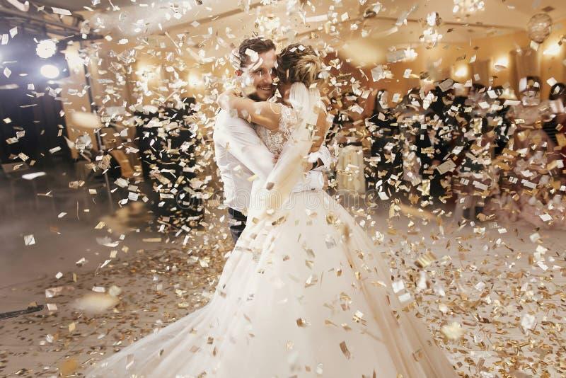 Ursnygg brud och stilfull brudgumdans under guld- konfettier a fotografering för bildbyråer