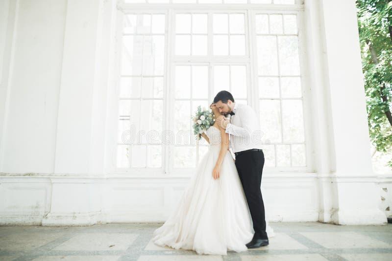 Ursnygg brudgum som kramar försiktigt den stilfulla bruden Sinnligt ögonblick av lyxiga brölloppar fotografering för bildbyråer