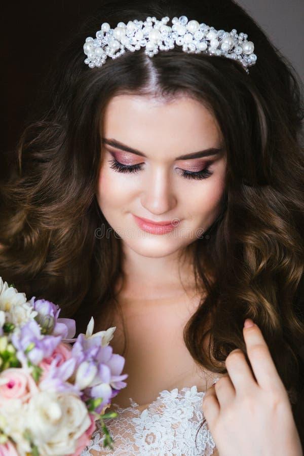Ursnygg brudst?ende H?rlig brud med att gifta sig makeup och smyckenkransen p? l?ngt lockigt h?r arkivbilder