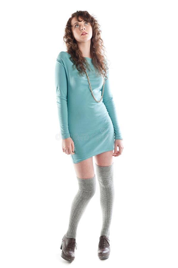 Ursnygg brunett i en turkosklänning som poserar i en studio arkivfoton