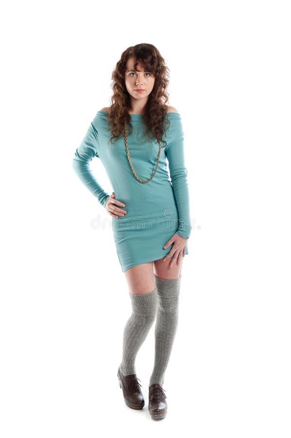 Ursnygg brunett i en turkosklänning som poserar i studion royaltyfria foton