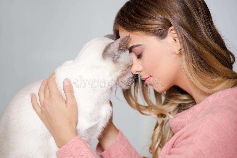 Ursnygg brunett med hennes katt fotografering för bildbyråer