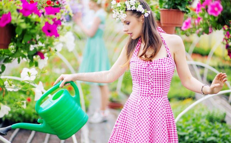 Ursnygg brunett som bevattnar blommorna royaltyfria bilder