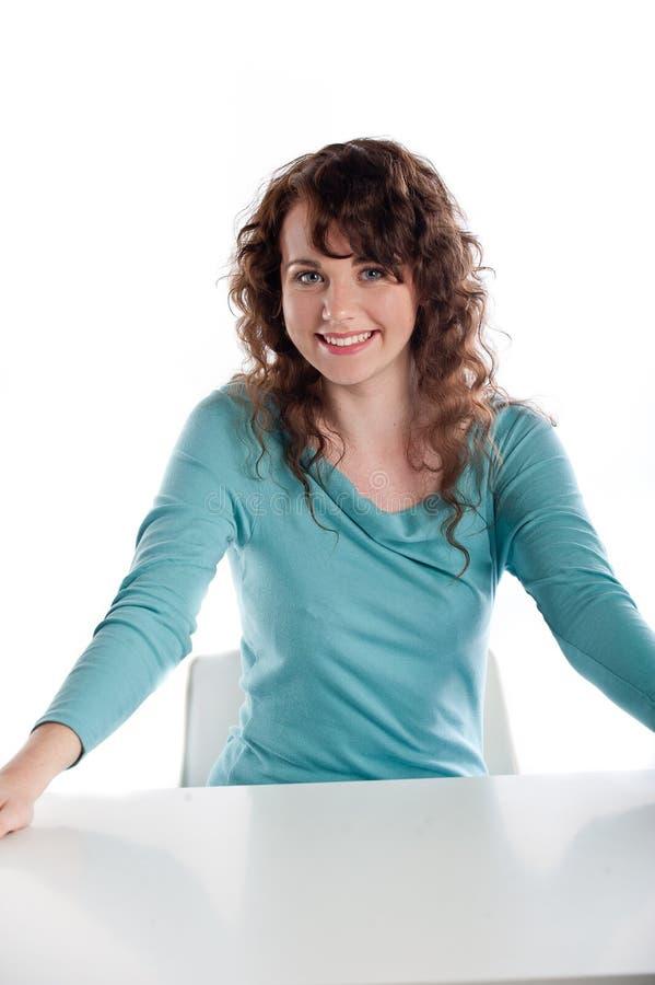 Ursnygg brunett som ler och poserar i en studio arkivbild