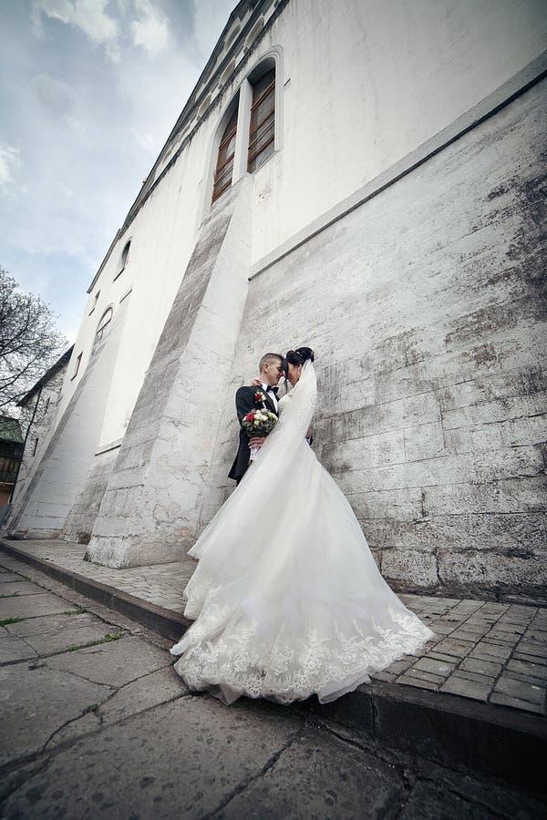 Ursnygg brunettbrud som kramar brudgummen och poserar nära gammal slott arkivbilder