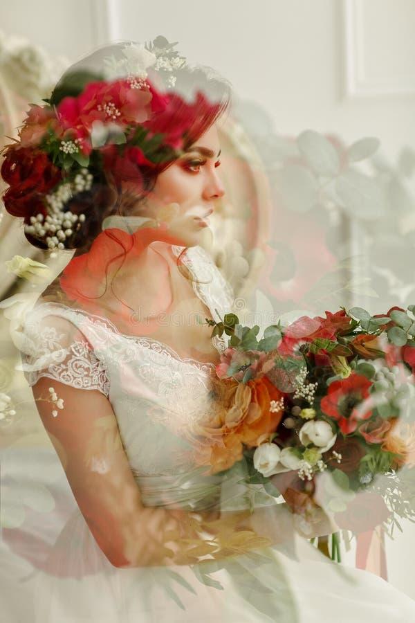 Ursnygg brunettflicka i en vit klänning, med en krans och en bou royaltyfria foton