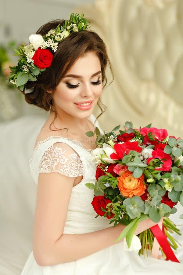 Ursnygg brunettflicka i en vit klänning, med en krans och en bou royaltyfria bilder