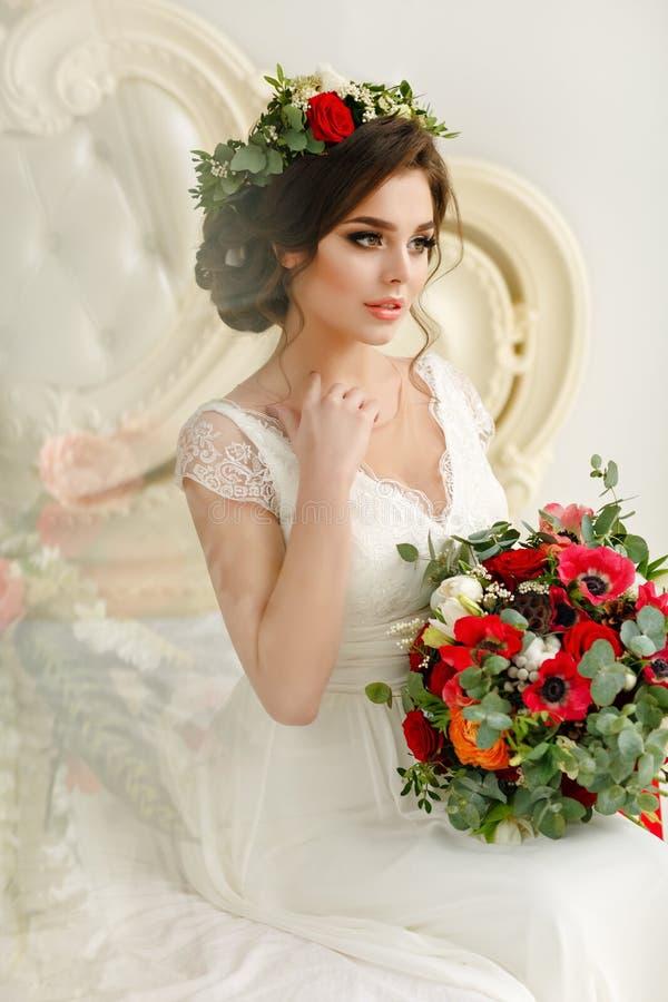 Ursnygg brunettflicka i en vit klänning, med en krans och en bou royaltyfri fotografi