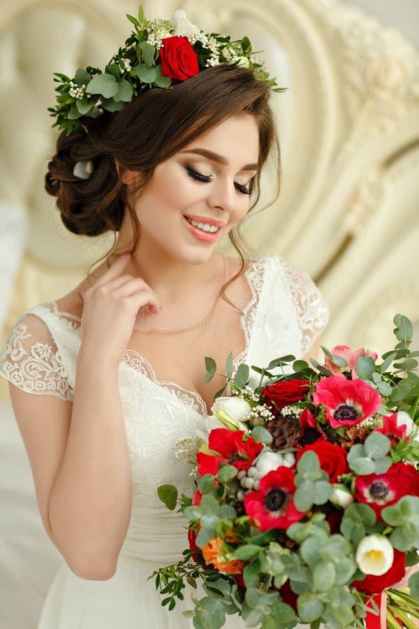 Ursnygg brunettflicka som ler i en vit klänning, med en krans a arkivfoton
