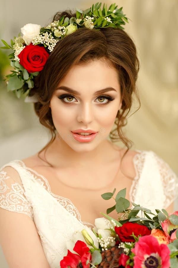 Ursnygg brunettflicka som ler i en vit klänning, med en krans a royaltyfria foton
