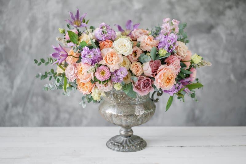 Ursnygg bukett av olika blommor blom- ordning i tappningmetallvas Table inställningen lila- och persikafärg royaltyfria foton