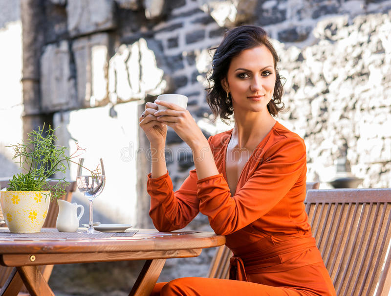 Ursnygg charmig flicka i den orange klänningen som har en kopp kaffe utanför arkivfoton