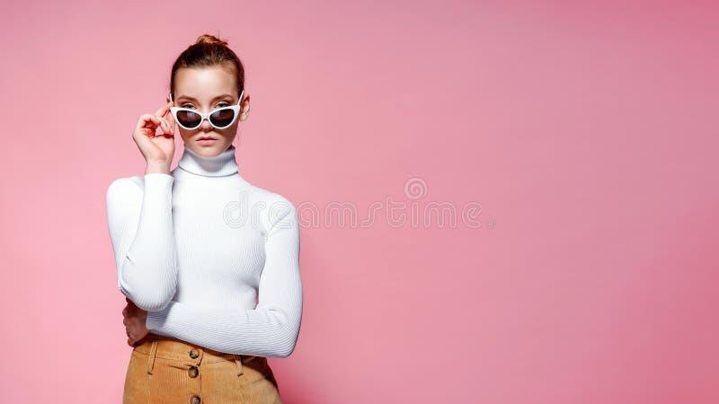 Ursnygg elegant kvinna i vit stucken golf och solglasögon som poserar över den rosa väggen royaltyfri bild