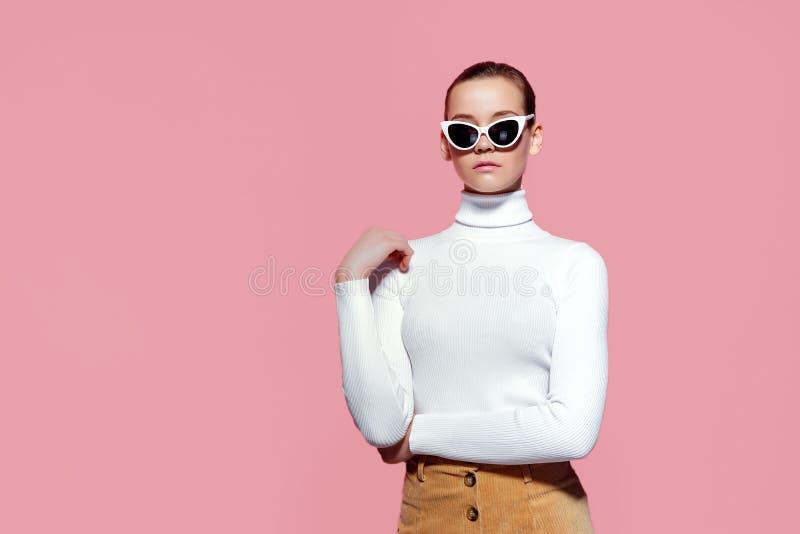 Ursnygg elegant kvinna i vit stucken golf och solglasögon som poserar över den rosa väggen arkivbild