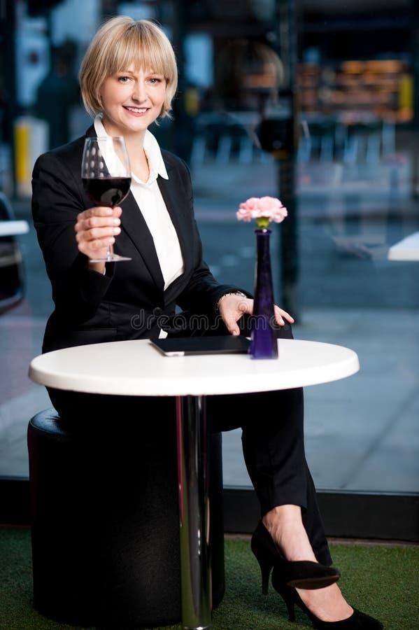 Ursnygg företags kvinna som tycker om rött vin royaltyfri foto