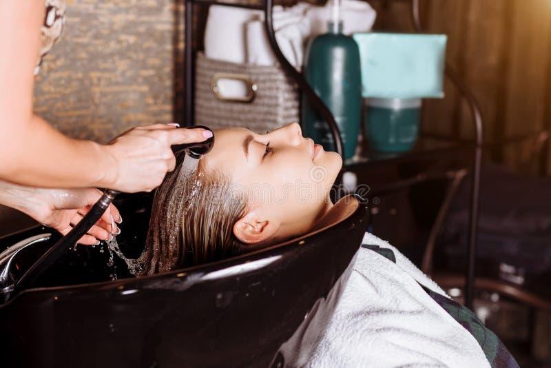 Ursnygg gullig ung kvinna som tycker om huvudmassage medan yrkesm?ssig fris?r som applicerar schampo hennes h?r St?ng sig upp av  arkivfoto