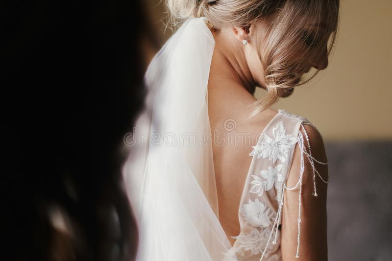 Ursnygg härlig brud som sätter på den stilfulla bröllopsklänningen på segern royaltyfri foto