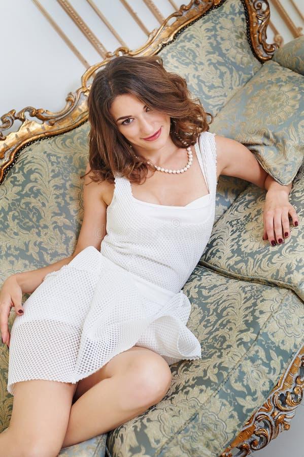 Ursnygg härlig ung kvinna som ligger på en soffa arkivbilder