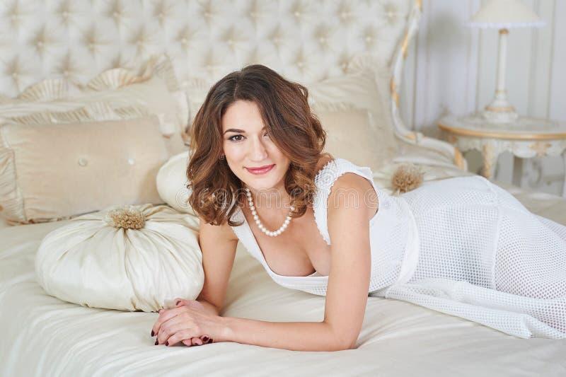 Ursnygg härlig ung kvinna som ligger på en soffa arkivbild