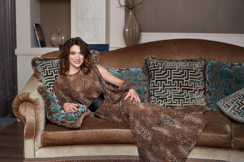Ursnygg härlig ung kvinna som ligger på en soffa arkivfoto