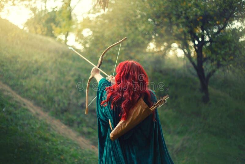 Ursnygg jägare som skjuter hennes sista ljus till solen, väntande på räddning under ruskig fara, rödhårig flicka royaltyfri bild