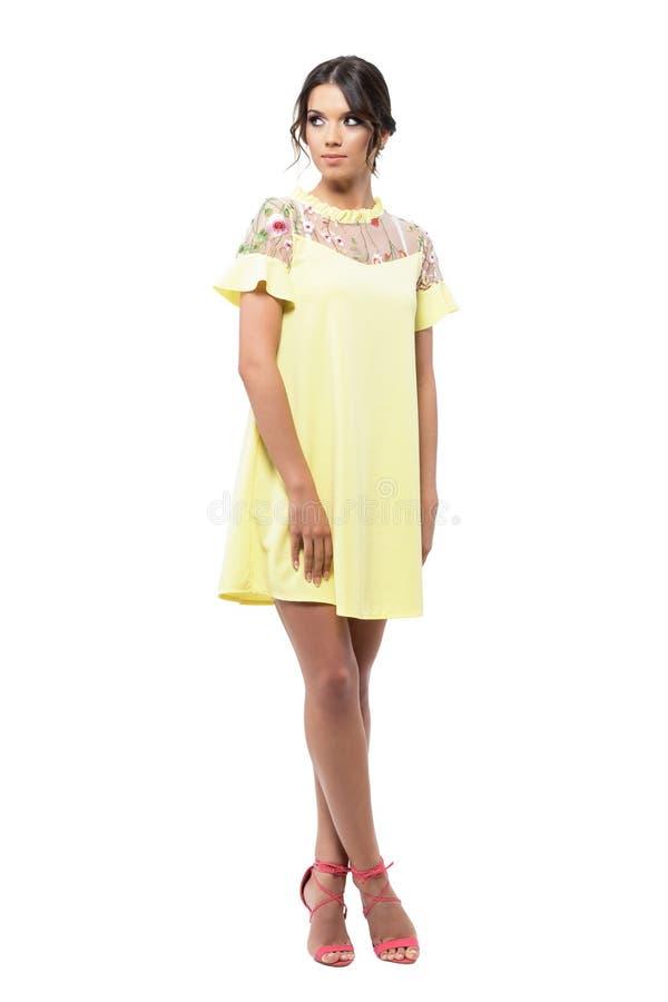 Ursnygg kvinna i den gula korta sommarklänningen som tillbaka poserar och ser över skuldran royaltyfria foton