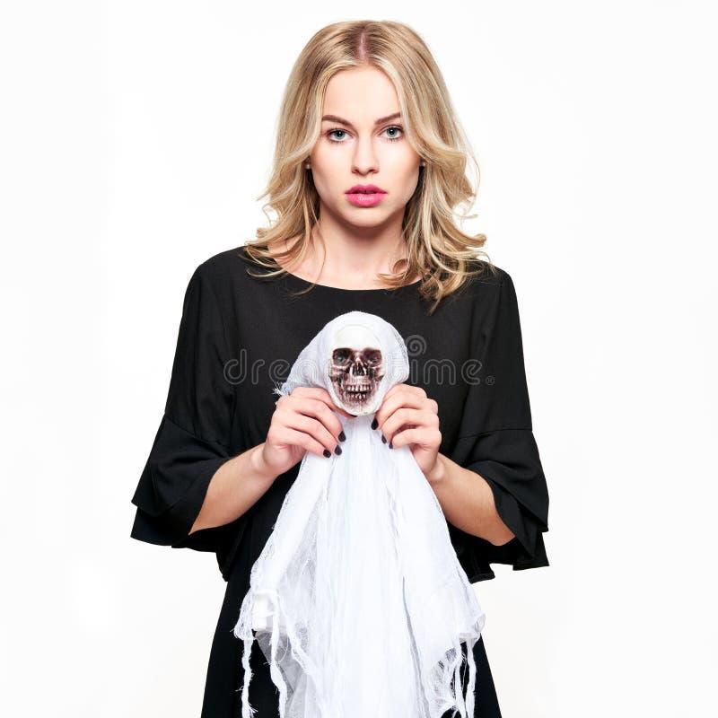 Ursnygg kvinna i garnering för skelett för allhelgonaafton för häxadräkt hållande för den grymma säger miniatyrreaperen halloween fotografering för bildbyråer