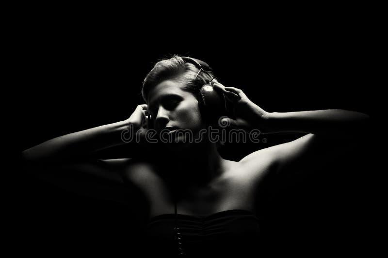 Ursnygg kvinna i svartvitt lyssna till musik arkivbild
