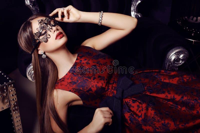 Ursnygg kvinna med mörkt hår i elegant klänning och maskering arkivbilder