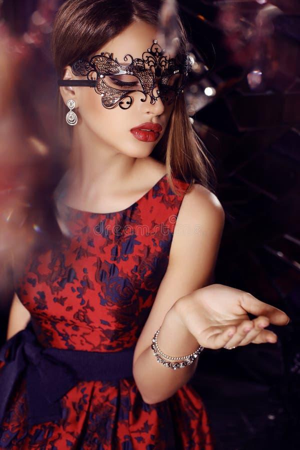 Ursnygg kvinna med mörkt hår i elegant klänning och maskering arkivbild