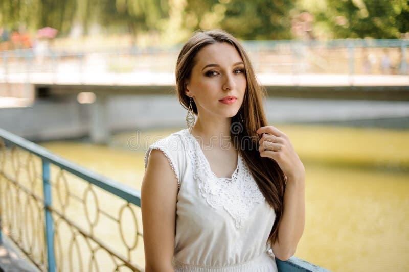 Ursnygg kvinna med mörkt hår i elegant vit klänning royaltyfri fotografi