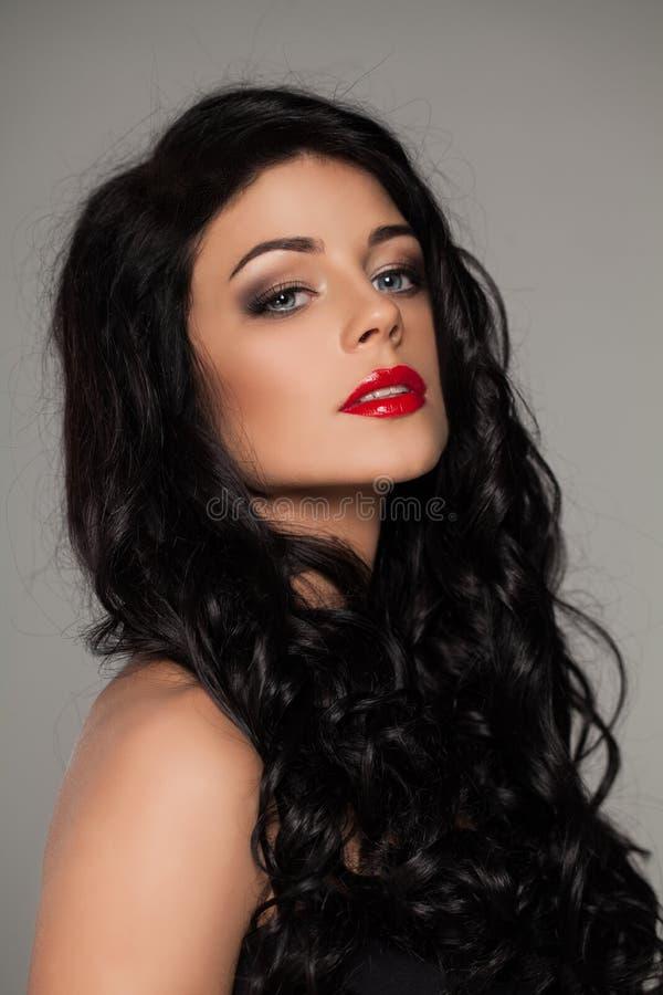 Ursnygg kvinna med mörkt lockigt hår och röda kanter royaltyfri bild