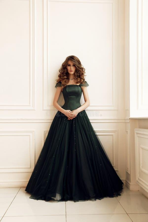 Ursnygg kvinna med makeup för mörkt hår och aftoni den eleganta klänningen som poserar i studio arkivbild